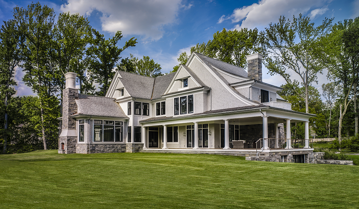 Symmetrical sweeping roofline in symmetrical shingel style home by Cardello Architects