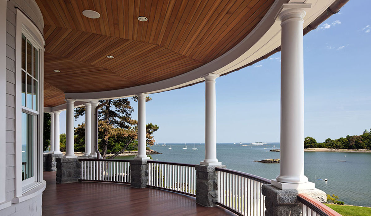 Waterfront covered porch on custom home design by luxury architect