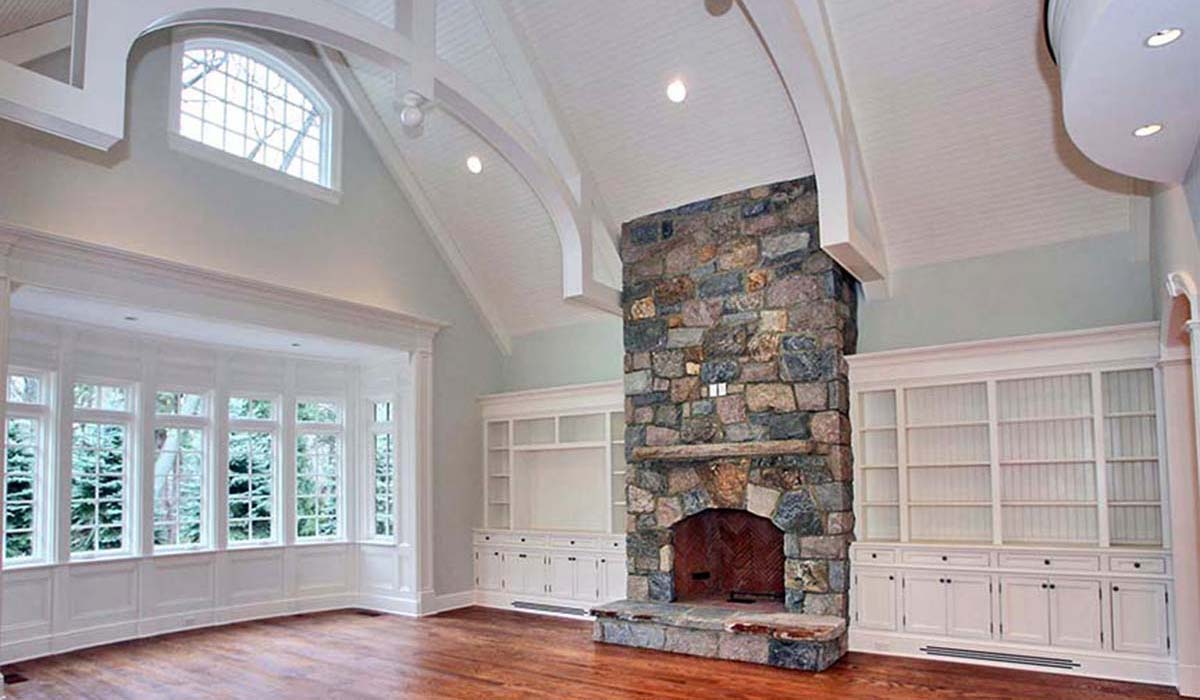 stone fireplace and hearth in classic shingel style home with decorative trusses by cardello architects