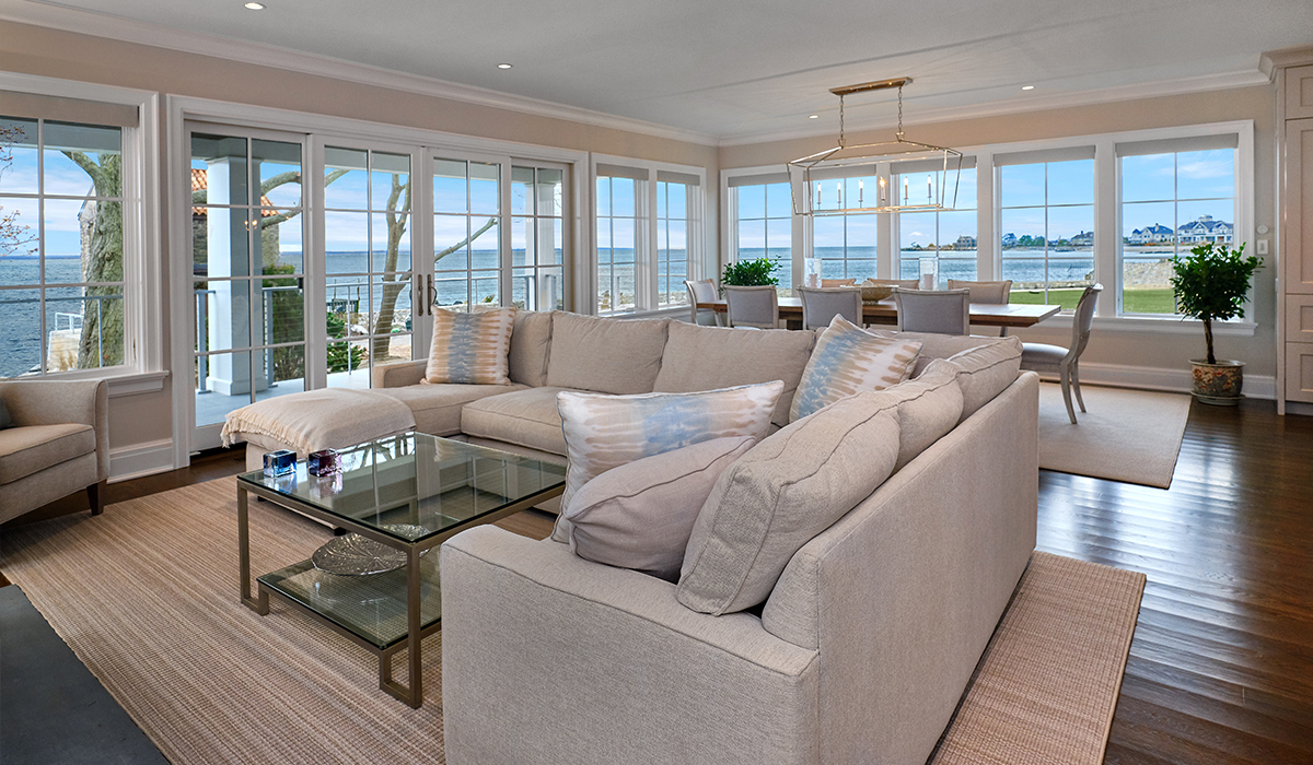 Open floor plan with living room and dining room overlooking Long Island Sound with waterfront views