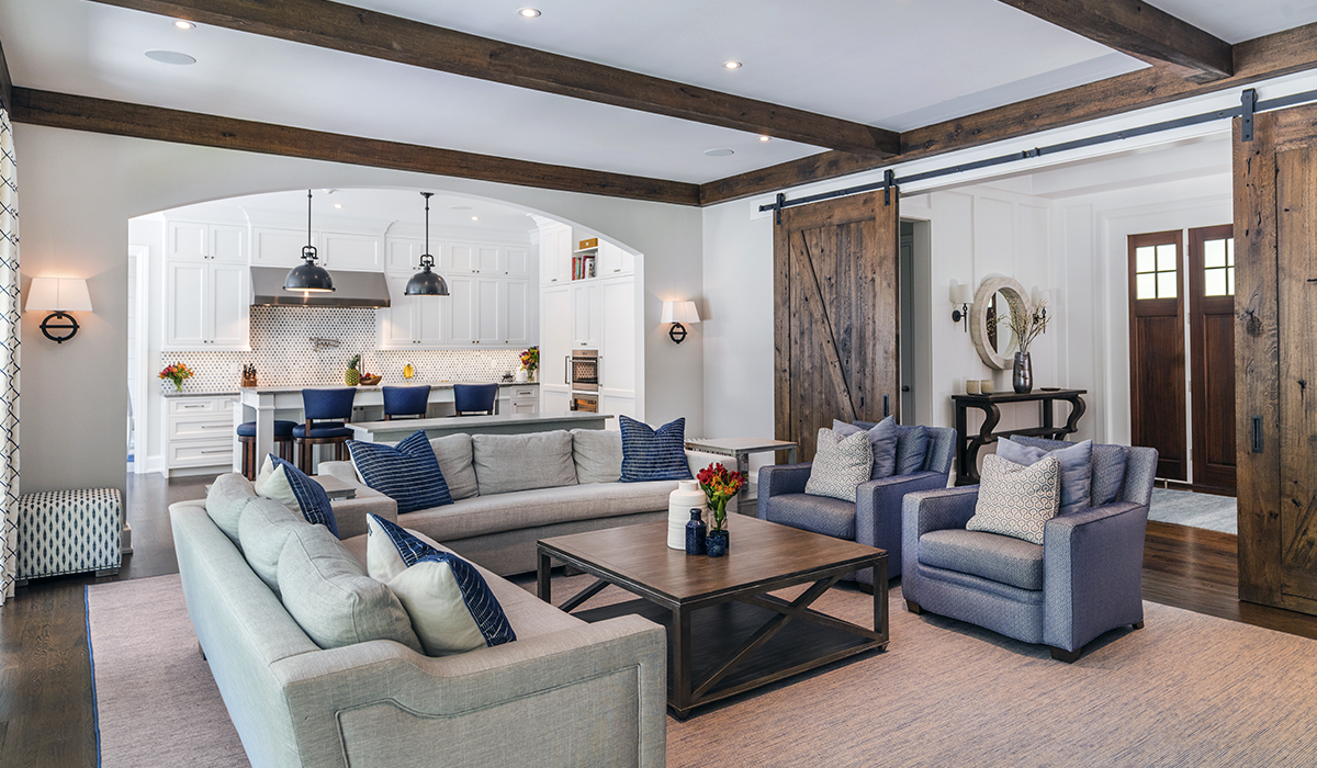 open floor plan living space with barn door in custom luxury shingle style home in New Canaan Connecticut by Cardello Architects