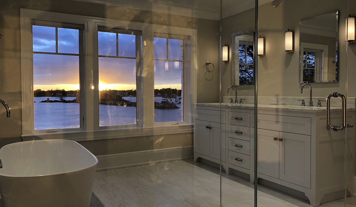master bathroom with soaking tub and glass shower with views of waterfront at sunset
